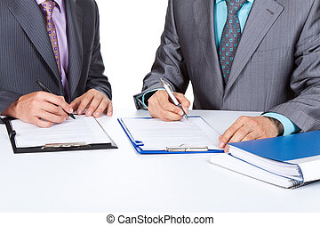 businessmen - Two business people working with documents...