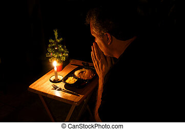 Lonely at Christmas - A man praying over a TV dinner at...