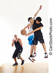 Three basketball players - Three young men playing...