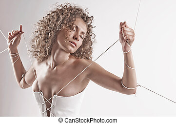 girl in white dress with her hands tied with rope - Photo of...