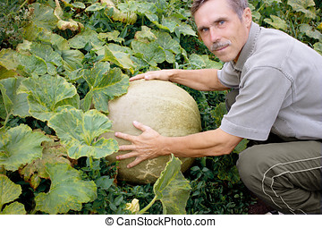 Pleased with the gardener and a large pumpkin