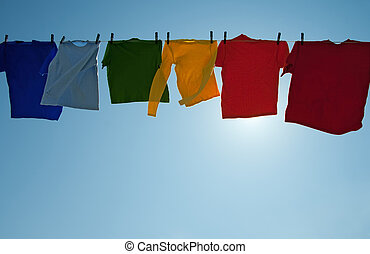 Sun shining through colorful clothes drying in the wind in...