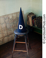 Old dunce cap on stool