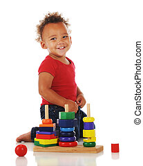 Little Puzzler - An adorable toddler playing with a stacking...