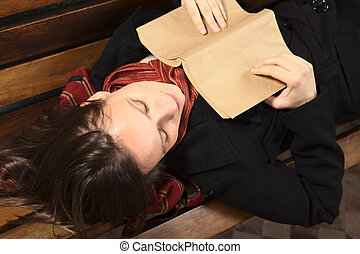 Young Caucasian woman lying on a bench reading