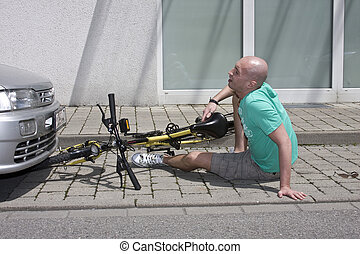 Bicycle Accident - A man is siting unconscious by the side...