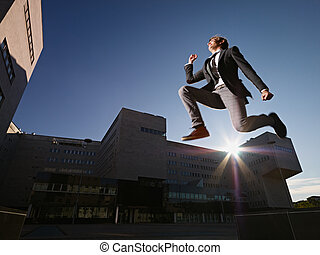 businessman jumping and smiling outside office - young...