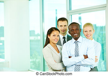 Office team - Four businesspeople looking at camera and...