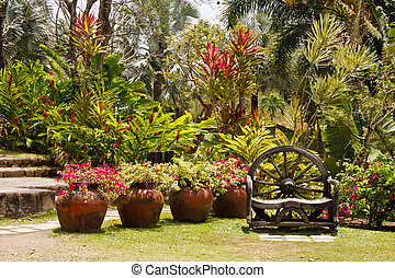 Hand Crafted Wood Bench in Lush Tropical Garden - A lush,...