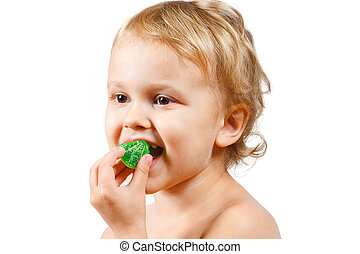 Little boy with green jelly candy on white background