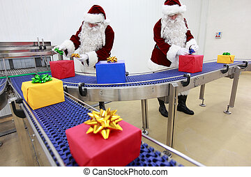 Two santa clauses working at produc