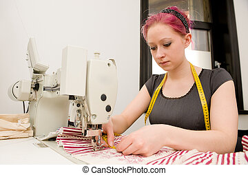Dressmaker with sewing machine in her studio