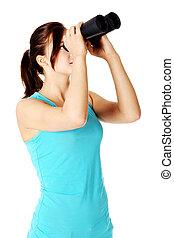 Young girl looking through binoculars - young caucasian girl...