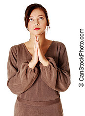 Yuong girl standing and praying - young pretty caucasian...