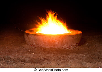 Fire pit at night - A blazing fire in a cement fire pit at...