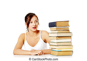 Young girl looking at the pile of books.