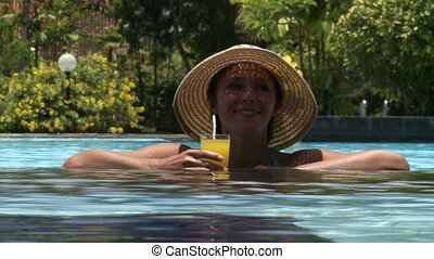 Orange juice   - Young woman in the pool with orange juice