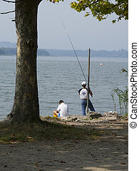 fishing on a lake - two men fishing on a lake with rod