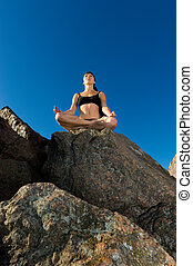 beautiful woman in lotus pose on the beach
