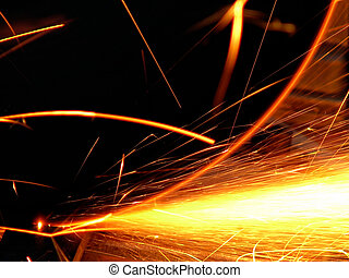 sparks - Cascade of red-and-yellow sparks on a dark...