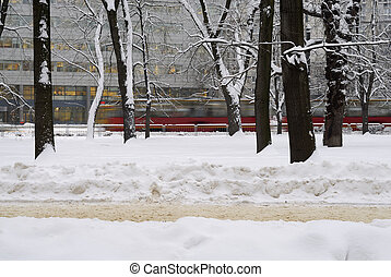 Tram rushing by trees in winter scene. - Blurred tram in the...