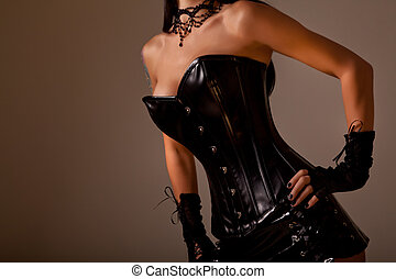 Close-up shot of busty woman in black leather corset, studio...