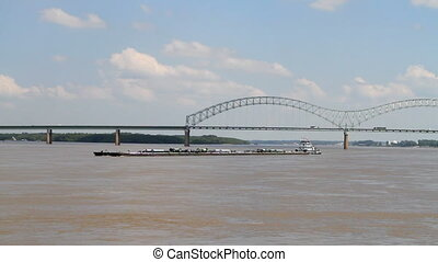 Barge On Mississippi - Tugboat pushes a barge down the...