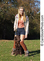 Girl and Dog - Pretty girl holding her flat-coated retriever...