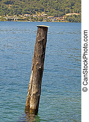 Pole of a pier stainding over a blue lake