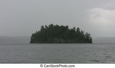 Stormy Island - Island on lake with rain and grey...
