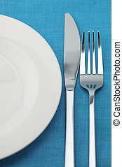 Set of tableware - Fork, knife and empty plate on blue...