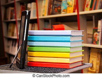 Stack of colorful books with electronic book reader
