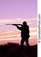 Hunter Shooting at Sunrise - a bird hunter shooting his...