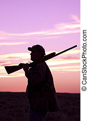 Upland Hunter in Sunrise - an upland game hunter with...
