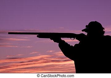 Shooting in Sunset - hunter shooting shotgun in the sunset