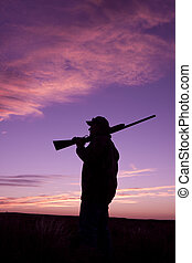 Hunter at Sunrise - a bird hunter with shotgun at sunrise