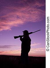 Hunter at Sunrise - a bird hunter with shotgun at sunrise