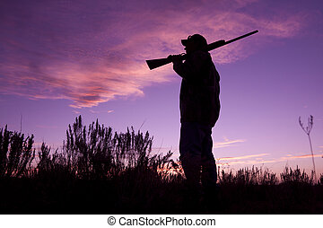 Hunter at Sunset - a hunter with gun in the sunset