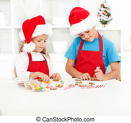 Kids decorating christmas cookies in the kitchen