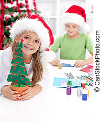 Kids making christmas decorations and postcards