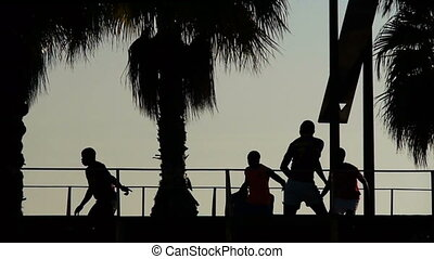 silhouettes of football players on a beach at sunset