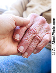 Helping hands - Young holding senior ladys hand
