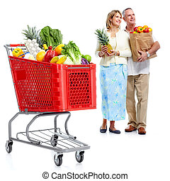 Happy couple with a shopping cart. - Happy senior couple...