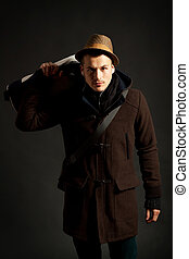 fashion male portrait with a hodded coat and a hand bag on...