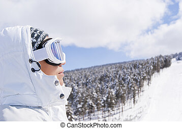 Portrait of beautiful skier looking forward on the route in...