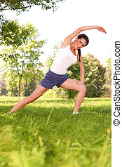 Young woman doing stretching exercise on green grass