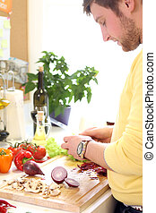 Young man cooking healthly food - Young and cheerful woman...