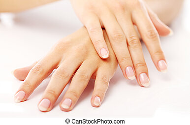 Beautiful hands with french manicure against white...