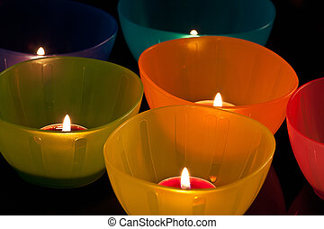 colored plastic cups with candles, close-up