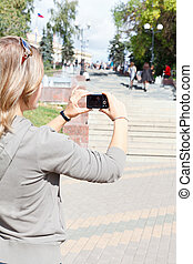 Young beautiful woman photographing city's attractions,...